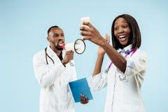 Los doctores afroamericanos felices de sexo femenino y de sexo masculino en fondo azul imagen de archivo