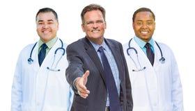 Los doctores Behind Businessman Reaching de la raza mixta para la sacudida de la mano encendido foto de archivo