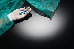 Los doctores dan sostener píldoras en fondo negro con el espacio de la copia Imágenes de archivo libres de regalías