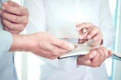 Los doctores de sexo femenino y los médicos de sexo masculino discuten la información de perfil paciente Imágenes de archivo libres de regalías