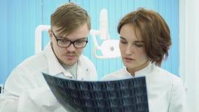 Los doctores de sexo femenino y de sexo masculino miran MRI media Dos doctores examinar y discutir la radiografía MRI del pacient metrajes