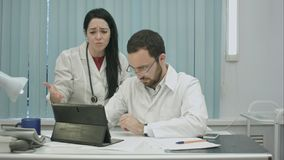 Los doctores de sexo masculino y de sexo femenino discuten resultados usando la tableta Imagen de archivo