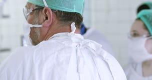 los doctores del equipo 4K en uniforme, vidrios y máscaras médicos están para las operaciones almacen de video