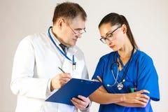Los doctores discuten qué régimen de tratamiento se adaptará al paciente y lo escribirá abajo en una carpeta fotos de archivo libres de regalías