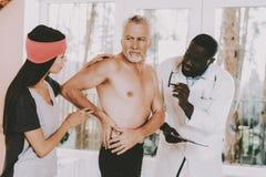 Los doctores Examine Body No haga eso backache back fotos de archivo