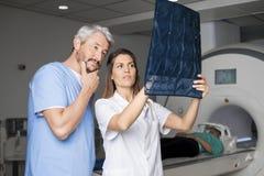 Los doctores Examining X-ray With Patient que miente en la máquina de la exploración del CT imagen de archivo libre de regalías