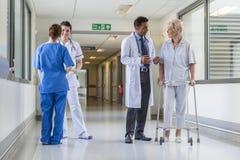 Los doctores Hospital Corridor Nurse Senior Female Patient Imágenes de archivo libres de regalías