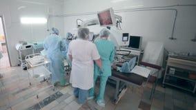 Los doctores irreconocibles combinan realizando cirugía en sala de operaciones del hospital almacen de video