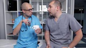 Los doctores jovenes hablan en el descanso para tomar café metrajes