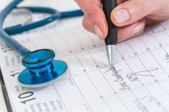 los doctores programados que es la cita escribieron en el calendario para el paciente Imagenes de archivo