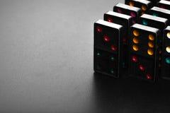 Los dominós negros del color con el juego colorido del punto juntan las piezas Imagenes de archivo