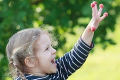 Los dos años felices de la muchacha rubia que muestra la frambuesa roja del jardín dan fruto Fotografía de archivo libre de regalías