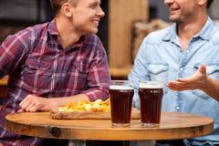 Los dos amigos masculinos atractivos están comunicando adentro Fotografía de archivo