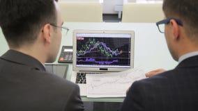 Los dos analytics de las finanzas trabajan en el informe final usando el ordenador portátil y el proyecto a estrenar