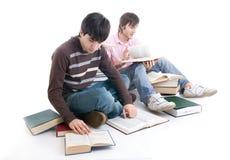 Los dos estudiantes con los libros aislados Foto de archivo