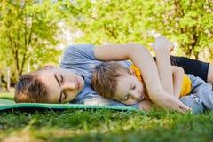 Los dos hermanos alegres duermen mentira en la hierba fotografía de archivo