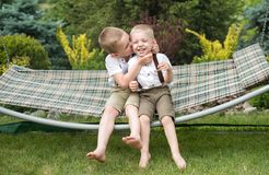Los dos hermanos est?n descansando y se est?n divirtiendo Los ni?os montan en una hamaca imagen de archivo
