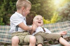 Los dos hermanos est?n descansando y se est?n divirtiendo Los ni?os montan en una hamaca fotos de archivo libres de regalías