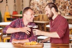 Los dos hombres atractivos están pasando tiempo en barra Imágenes de archivo libres de regalías