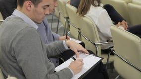 Los dos hombres de negocios se sientan entre sus colegas en la presentación del negocio y toman notas sobre los papeles metrajes
