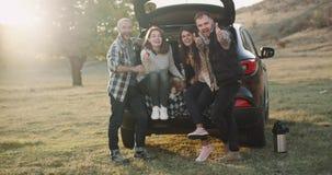 Los dos pares muy hermosos juntos en un viaje con el coche tienen una parada, ellos que se sientan en el tronco del coche y felic almacen de metraje de vídeo
