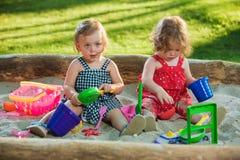 Los dos pequeños bebés que juegan los juguetes en arena Foto de archivo