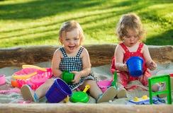 Los dos pequeños bebés que juegan los juguetes en arena Fotografía de archivo libre de regalías