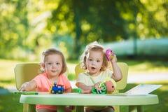 Los dos pequeños bebés que juegan los juguetes en arena Imagen de archivo