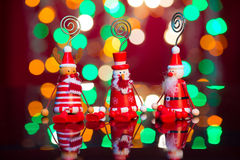 Los duendes, santa y el muñeco de nieve de la Navidad juegan con el fondo de las luces Fotografía de archivo libre de regalías