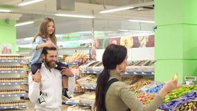 Los dulces de la compra de la familia en la tienda, la hija se sientan en los hombros de su padre metrajes