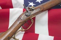 Los E.E.U.U. señalan el rifle por medio de una bandera antiguo revolucionario patriótico Fotografía de archivo