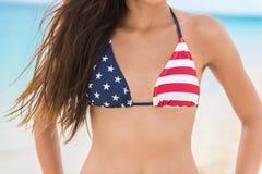 Los E.E.U.U. señalan a la mujer atractiva del bikini por medio de una bandera el vacaciones de la playa imagen de archivo