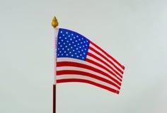 Los E.E.U.U. señalan pequeño por medio de una bandera en el fondo blanco Imagen de archivo