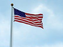 Los E.E.U.U. señalan por medio de una bandera con el cielo azul y se nublan el fondo Imagenes de archivo
