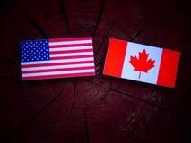 Los E.E.U.U. señalan por medio de una bandera con la bandera canadiense en un tocón de árbol aislado imagenes de archivo