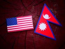 Los E.E.U.U. señalan por medio de una bandera con la bandera del Nepali en un tocón de árbol aislado imágenes de archivo libres de regalías