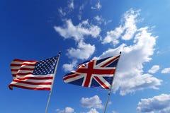 Los E.E.U.U. y banderas BRITÁNICAS en el cielo azul Imágenes de archivo libres de regalías