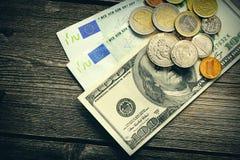 Los E.E.U.U. y dinero euro sobre fondo de madera imagen de archivo libre de regalías