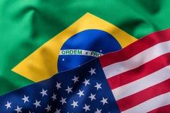 Los E.E.U.U. y el Brasil Los E.E.U.U. señalan una bandera del Brasil por medio de una bandera Imagen de archivo