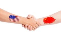 Los E.E.U.U. y manos de China que sacuden con las banderas Imagenes de archivo