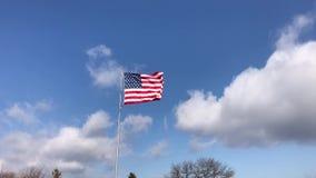 Los E.E.U.U. americanos señalan agitar por medio de una bandera con el cielo azul y las nubes almacen de metraje de vídeo