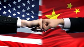 Los E.E.U.U. contra el conflicto de China, crisis de las relaciones internacionales, puños en fondo de la bandera fotografía de archivo