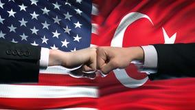 Los E.E.U.U. contra el conflicto de Turquía, crisis de las relaciones internacionales, puños en fondo de la bandera almacen de video
