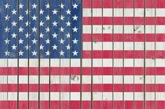 Los E.E.U.U. señalan por medio de una bandera pintado en la cerca de madera, fondo americano foto de archivo