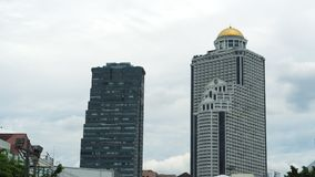 Los edificios de oficinas en el centro de ciudad en el fondo del cielo nublado, enfocan adentro almacen de metraje de vídeo