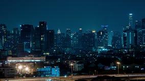 Los edificios en noche de la ciudad y la raya pálida trafican, lapso de tiempo metrajes