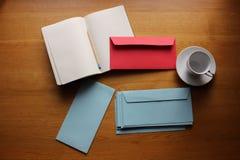 Los efectos de escritorio fijaron con los sobres, el cuaderno, el lápiz y una taza Fotografía de archivo libre de regalías