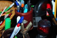 los efectos de escritorio varían las plumas, lápices, borradores, sellos llenaron todo para arriba imagen de archivo libre de regalías