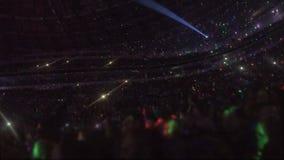 Los efectos luminosos asombrosos en la arena con millares de gente que disfruta de música muestran metrajes