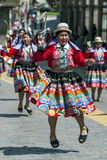Los ejecutantes colorido vestidos bailan abajo de una calle de Cusco durante el desfile del primero de mayo en Perú Imágenes de archivo libres de regalías